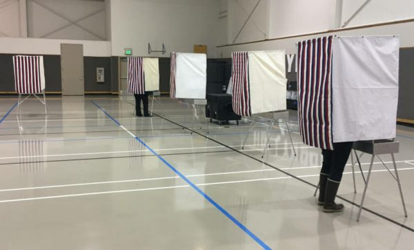 Voting booths spaced 6 feet apart in an open gym. People are voting inside them with their legs visible