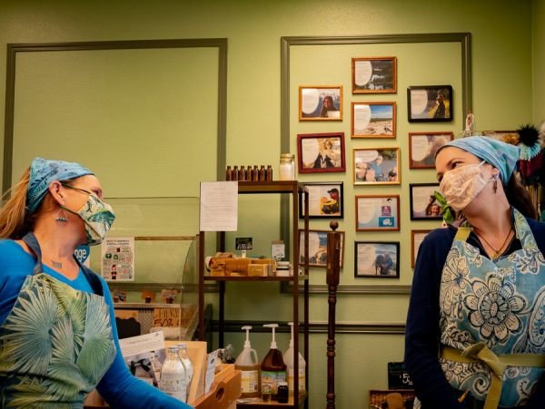 Two women wearing aprons and masks stand in front of shelves in a store