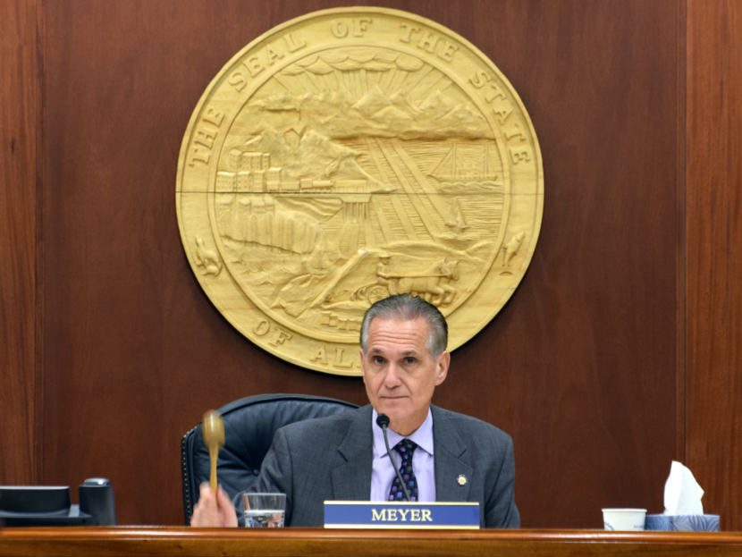A white man in a gray suit beneath a gold state of alaska seal