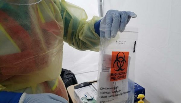 A public health worker in a tent outside Juneau International Airport bags a freshly collected nasal swab for COVID-19 testing.
