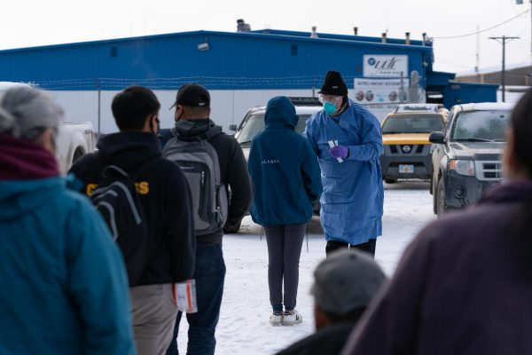 A health worker in a blue gown swabs travelers waiting in line outside the bethel airport