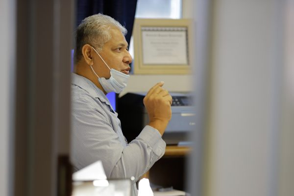 A grey-haired samoan man in a stripped button up shirt and a mask below his nose speaks in his office as seen through a crakc in the door