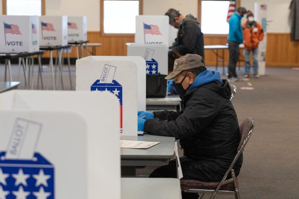 An Alaska Native man in a baseball cap sits at a voting booth
