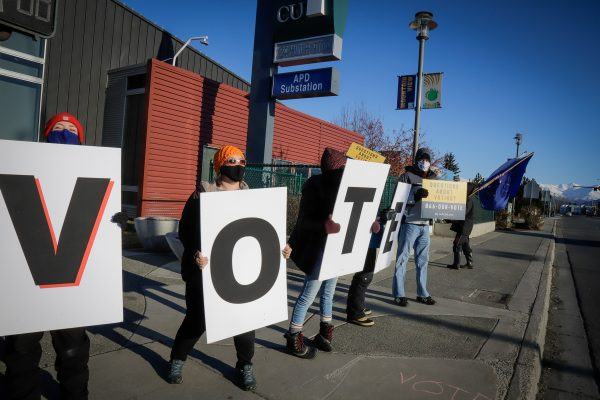 """people hold up signs that spell out """"VOTE"""""""
