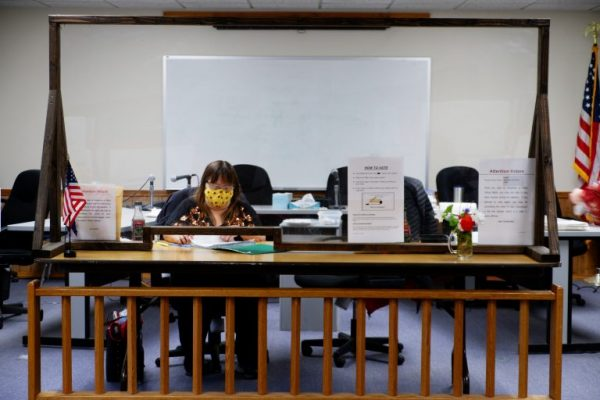 A poll worker in a mask sits behind a wooden desk