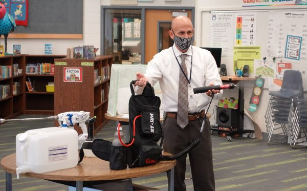 Rob Holland, Anchorage School District director of maintenance and operations, describes the different sanitation equipment that will be used at schools. He is holding a high-volume disinfectant sprayer.