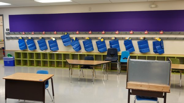 Bags hang on coat hooks for students to use to store their outdoor gear.
