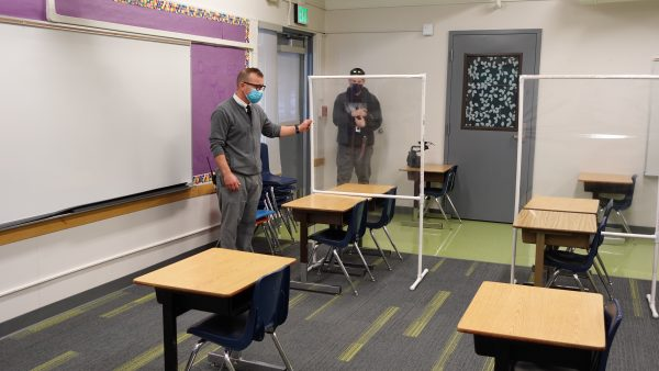 Huffman Elementary School principal Chris Opitz stands in a classroom pointing to a barrier that's between students' desks.