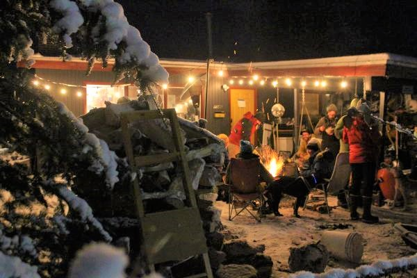 A group of friends sits around a fire outside to enjoy socializing despite COVID-19 and the winter cold.