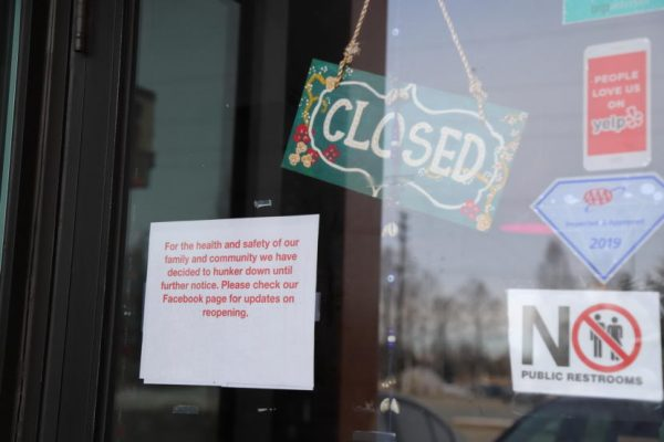 Signs in a window announce covid closures