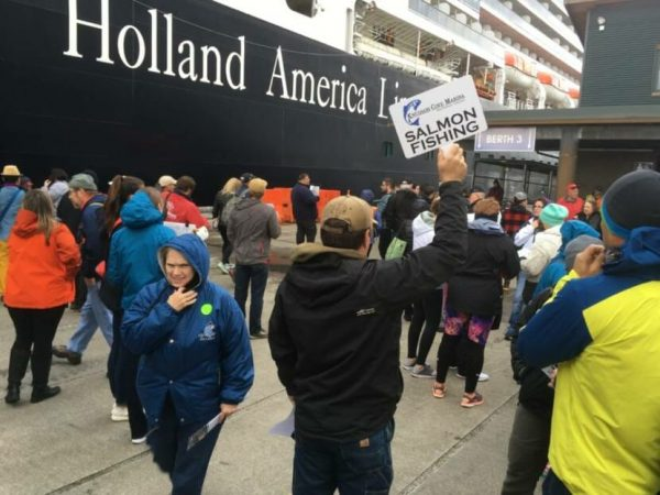 Crowds of people at the dock next to a Holland American ship