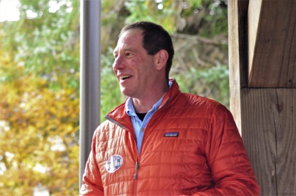 A white man in a orange patagonia jacket standing next to a window