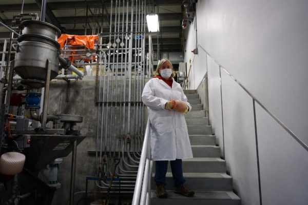 A woman in a white lab coat stands on a stairway