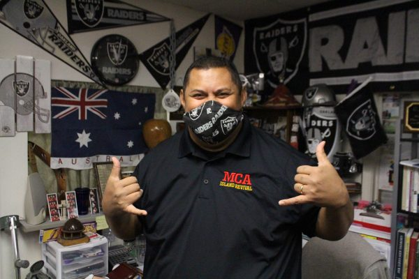 A samoan man in a black collared t-shirt and a black oakland raiders mask gives a 'shaka' sign at his desk.