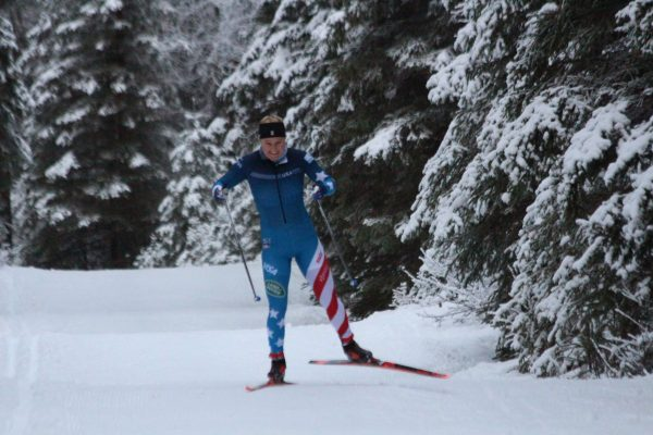 A skier in a blue and red white striped race uniform skis on a snowy trail with spruce trees around