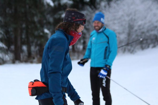 A skier in a blue jacket and red face covering talkks with another sksier standing with a lighter blue jacket