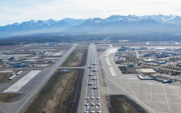 A runway with a dozen fighter jets anda mountains in the background