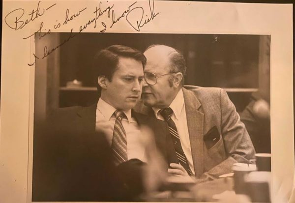 In a black and white photo, two white men talk seated at a table