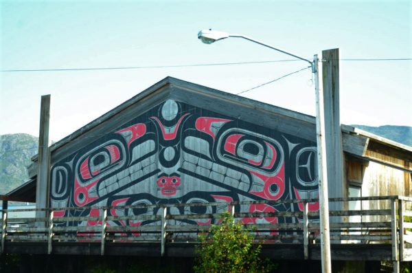 A structure, with mountains in the background, painted with Tlingit art.
