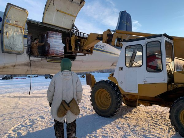 In Tanana, a man in a parka waits to help a pilot unloads boxes of donated dog food from a small plane.