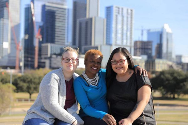 From left to right, a white woman, a black woman and an Alaska Native woman with their arms on each other's shoulders, smiling and posing for a photo with skyscrapers in the background.