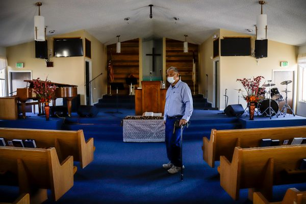 A grey-haired samoan man with a cane stands in the middle of several pews on a blue floor