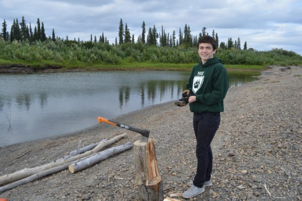 A young man from the Northwest Arctic, who attends Harvard and was recently accepted as a Rhodes Scholar, stands by the Kobuk River.