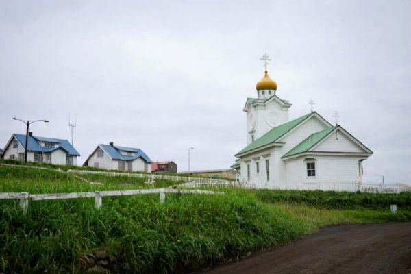 A white wooden church with a golden onion dome