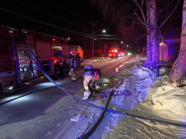A firefightes leans over a hose on a snowy road next to a fire truck.