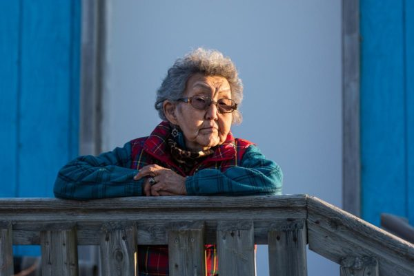 An Alaska Native woman rests her arms on a railing.