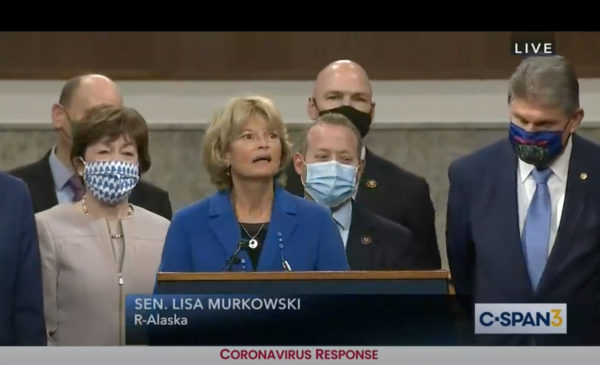 Sen. Lisa Murkowski speaks behind a podium, flanked by a bipartisan group of moderate senators.