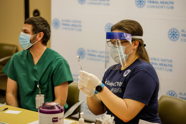 a person wearing a face shield and mask prepares to administer a shot to someone wearing scrubs and a mask