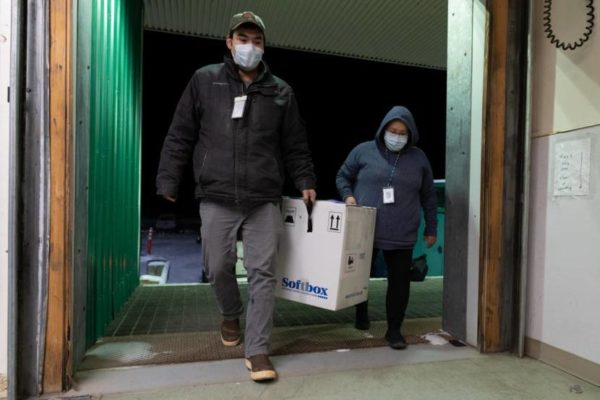 Two people carry a large box into a walk-in freezer.