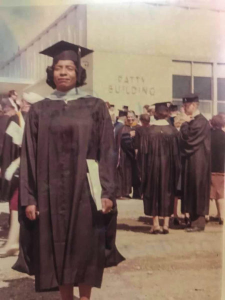 an old photo of a Black woman in a graduation gown in front of a mostly white crowd