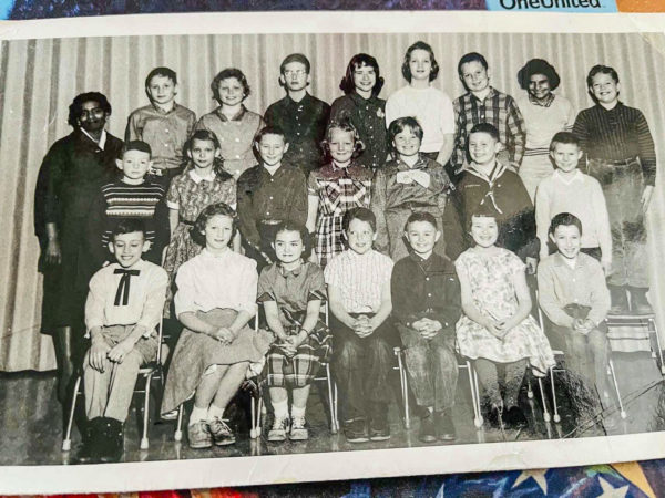 a class photo from 1960 of a teacher and students