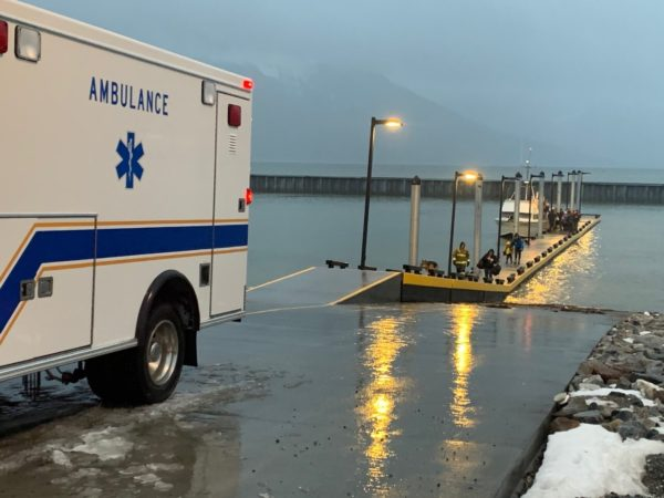 An ambulance backing into a dock on a rainhy day