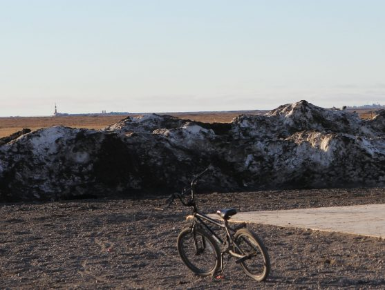 A bicycle parked with oil rigs visible in the backfroung