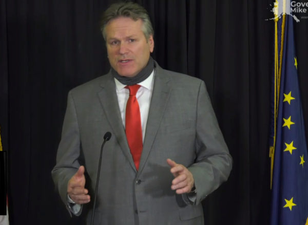 A white man in a gray suit gestures in front of a microphone