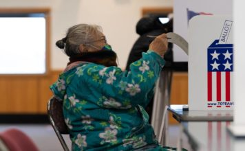 A woman in a flowery parka and a mamsk puts her ballot in a box