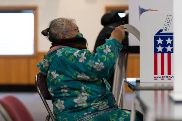 A Bethel woman in a flowery parka and mask reads her ballot.