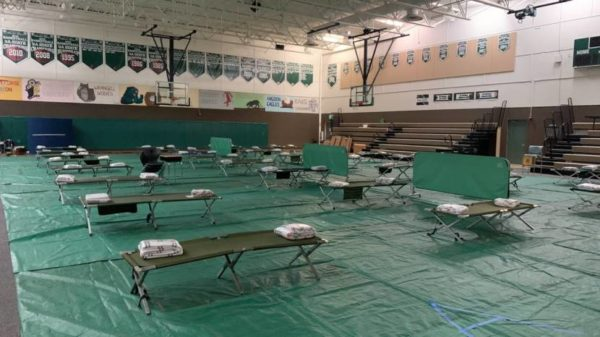 A gym floor covered in tarps and cots for evacuated residents.