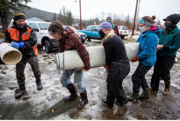 Several people carry a rolled up carpet in a muddy road