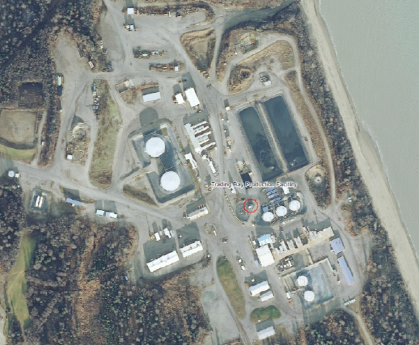 An aerial view of an oil production facilities shows a series of buildings near the Cook Inlet waters