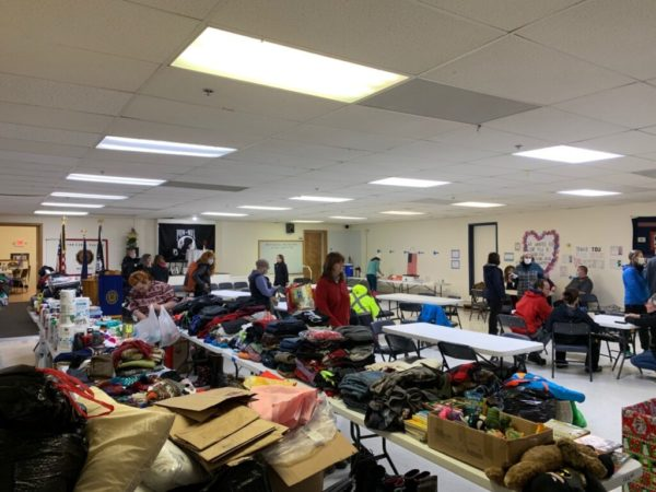 Tables filled with emergency clothes and supplies in a low-ceilinged room