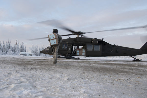 A masked man carries a box on a snoowy ground from his helicopter