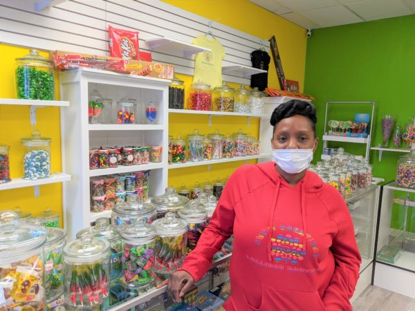 A Black woman stands in front of a counter with medium-sized jars of filled with candy