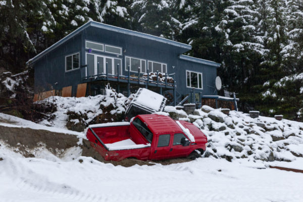 A truck below a house that is partially on its side and covered with light snow