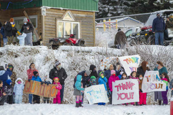 A group of residents hold signs in a snowy scene that say thank you