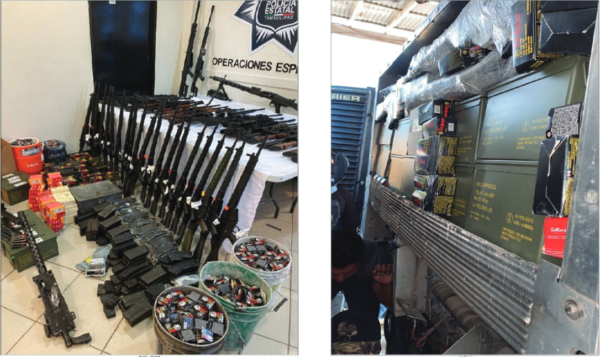 About two dozen guns sitting or propped up on a table in a line and buckets of ammunition.