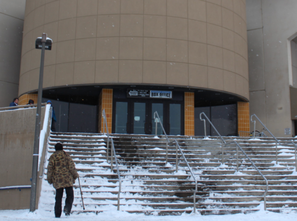 A man walks up a concrete staircase in snowy weather